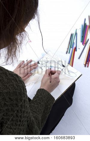 Young girl artist drawing pencils on white background