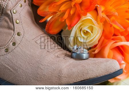 Boot and wedding rings with fall flowers in the background