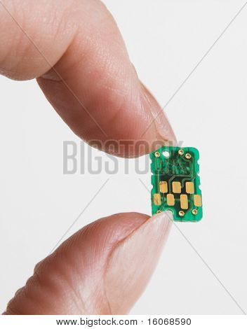 Tiny computer chip held by two fingers