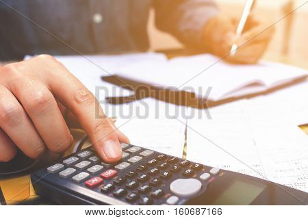 Close up hand man using calculator and make note in home office.