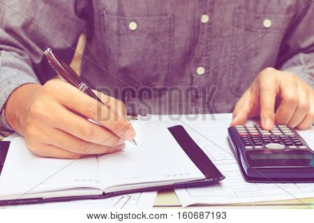 Man using calculator and writing note in home office.