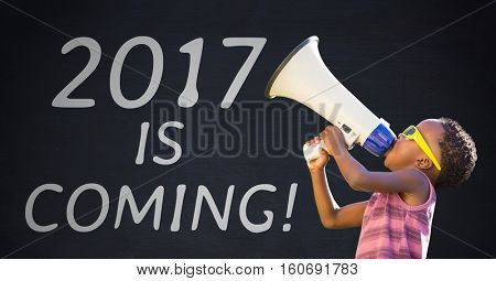 Boy with megaphone against 2017 new year sign on black background