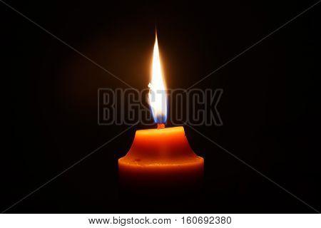 yellow candle isolation on black background photo