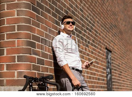 people, technology and lifestyle - happy young man with headphones, smartphone and bicycle listening to music in city