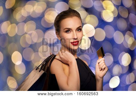 people, luxury and sale concept - beautiful woman with credit card and shopping bags over blue holidays lights background
