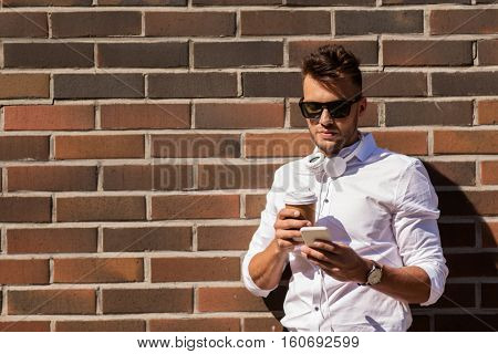 technology and people concept - young man in sunglasses with smartphone and coffee cup on city street