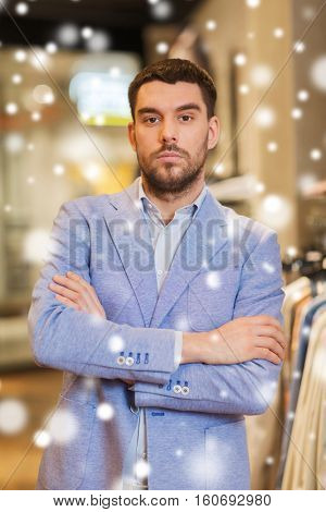 sale, shopping, fashion, style and people concept - young handsome man in jacket at clothing store over snow