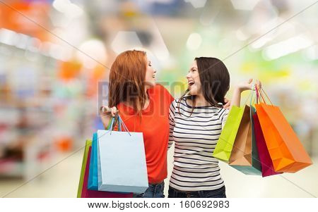 sale and people concept - two smiling teenage girls with shopping bags over supermarket background