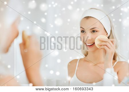 beauty, skin care and people concept - smiling young woman   in hairband washing her face with facial cleansing sponge at bathroom over snow