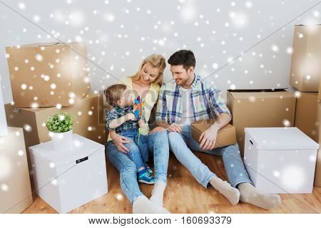 mortgage, people, housing and real estate concept - happy family with boxes moving to new home over snow