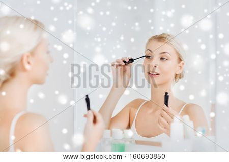 beauty, make up, cosmetics, morning and people concept - smiling young woman applying eye makeup with mascara and looking to mirror at home bathroom over snow
