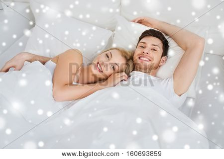 people, rest, love, relationships and happiness concept - happy smiling couple lying in bed at home over snow