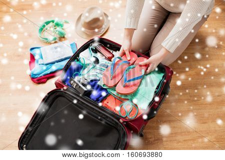 winter holidays, vacation, tourism and people concept - close up of woman packing bag with summer clothes and travel stuff over snow
