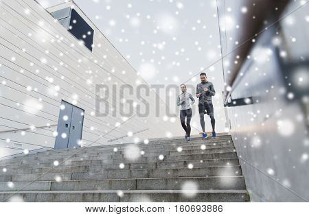 fitness, sport, people, exercising and healthy lifestyle concept - couple of sportsmen running downstairs outdoors over snow