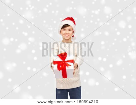 winter holidays, presents, christmas, childhood and people concept - smiling happy boy in santa hat with gift box over snow background