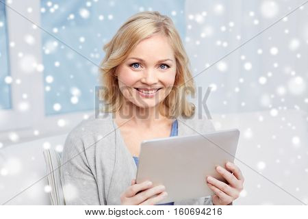 people, technology and internet concept - happy middle aged woman with tablet pc computer at home over snow