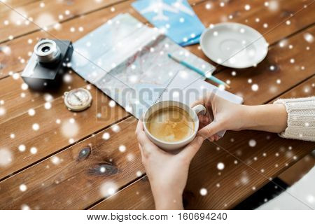 vacation, tourism, winter holidays and people concept - hands with coffee cup and travel stuff over snow