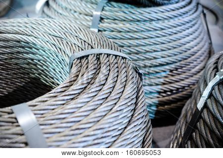Coils of steel cable. Several steel wire rope rings stacked on the floor.