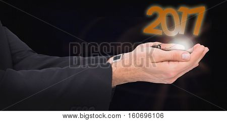 Businessman with arms out presenting something against dark background