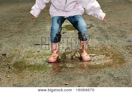 Feet of a little girl jumping into a muddy puddle