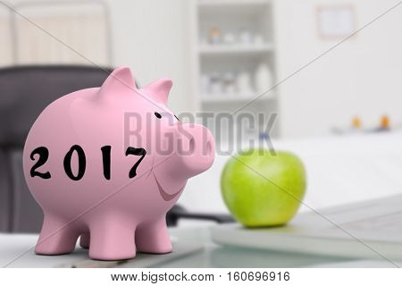 Green apple placed on a laptop near a clipboard against digital image of new year 2017