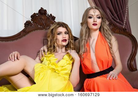 two beautiful girls in dresses sitting in a restaurant