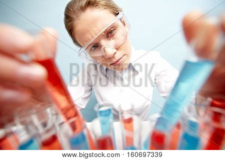 Young woman in safety glasses and a lab coat at work in a laboratory holding a test tube