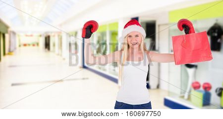 Festive blonde cheering with boxing gloves against image of blurry shop