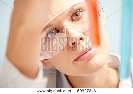 Young woman in protective eyewear examining test tube