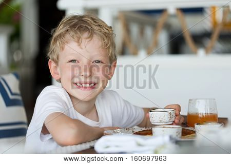 little serious boy enjoying breakfast at vacation at hotel or resort