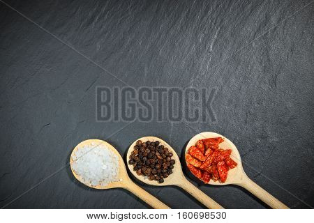 Spices In Wooden Spoons Over Black Stone Background, Top View With Copy Space