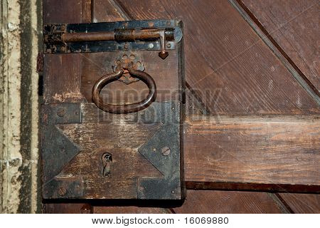 Antique rusty lock on a medieval wooden door