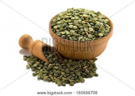 Green peas in a wooden bowl with a spatula. Isolated