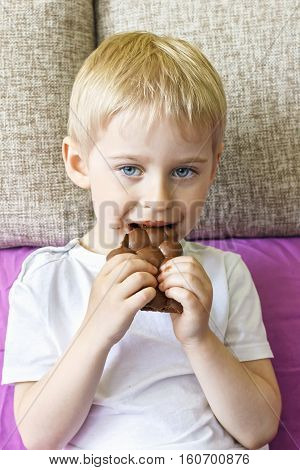 Little Boy Eating Chocolate, Blond With Blue Eyes