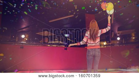 Rear view of hipster woman holding balloons against flying colours