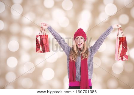 Festive blonde holding shopping bags against circle design on light background