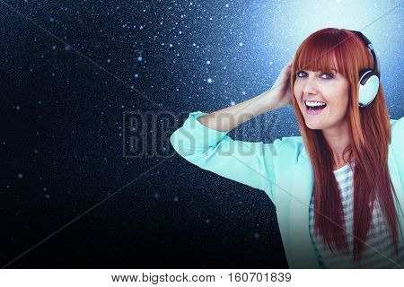 Happy hipster woman listening music with headphone against snowflake pattern