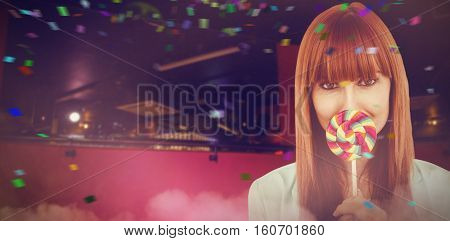 Smiling hipster woman with a lollipop against flying colours