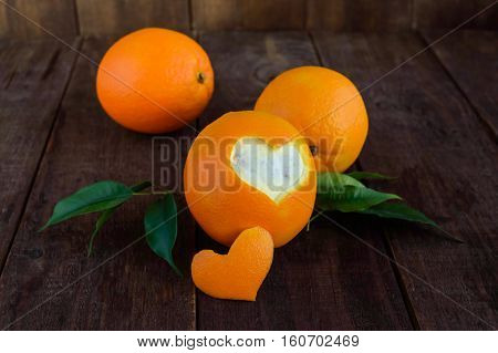 A few ripe oranges with leaves on a dark wooden background. One cut orange peel in the shape of a heart.