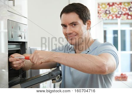 Portrait Of Repairman Fixing Domestic Oven In Kitchen