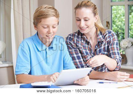 Female Home Tutor Helping Boy With Studies Using Digital Tablet
