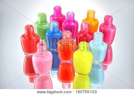 Open bottles with bright nail polish on grey background. Close up.