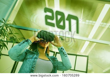 Digital image of new year 2017 against low angle view of businesswoman enjoying virtual reality headset at office