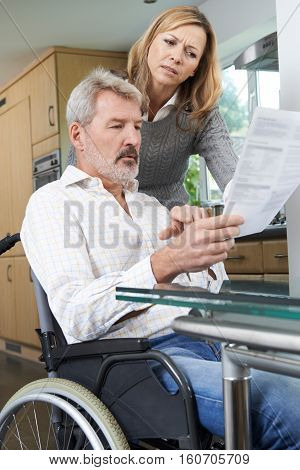 Couple With Husband In Wheelchair Reading Letter