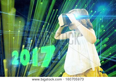 Girl wearing virtual reality simulator against digitally generated black and blue matrix
