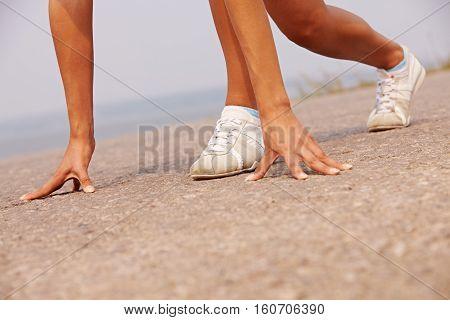 female runner standing on start in nature outdoors
