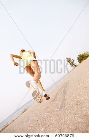 athletic woman running in nature outdoors from behind