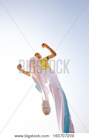 female doing broad jump in nature outdoors