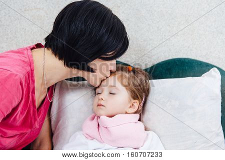 Mother kissing sick daughter forehead. Healthcare concept