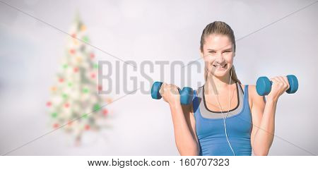 Pretty fit woman against blurry christmas tree in room